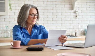 Fototapeta Adult senior 60s woman working at home at laptop. Serious middle aged woman at table holding document calculating bank loan payments, taxes, fees, retirement finances online with computer technologies
