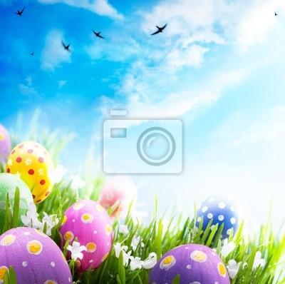 Art Velikonoční vajíčka zdobená květinami v trávě na modré obloze