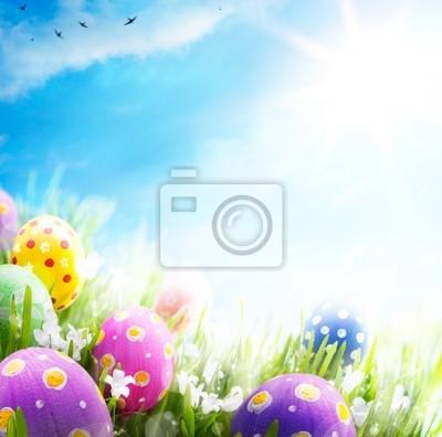 Fototapeta Art Velikonoční vajíčka zdobená květinami v trávě na modré obloze