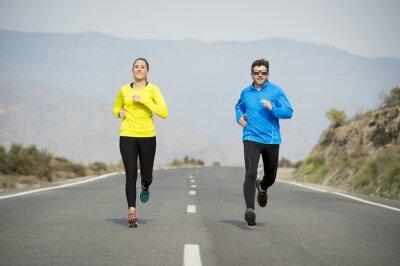 Fototapeta Atraktivní sportovní dvojice muž a žena běží společně na asfaltové silnice horské krajiny