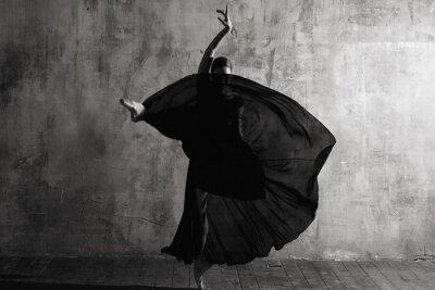 Fototapeta Ballerina in ballroom. Ballet dancer in studio. Black and white monochrome.