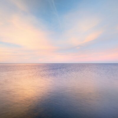 Fototapeta Baltic sea under the colorful sunset sky. Stunning seascape. Golden sunset light through the pink clouds. Long exposure. Tranquility scene. Riga bay, Latvia