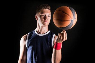Fototapeta Basketbalový hráč točící se míček na prst
