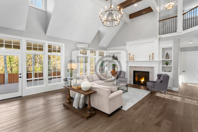 Fototapeta Beautiful living room in new traditional style luxury home. Features vaulted ceilings, fireplace with roaring fire, and elegant furnishings.