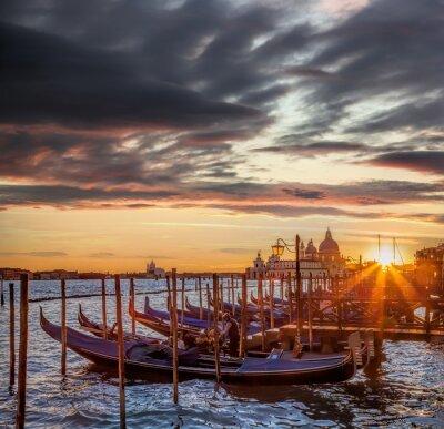 Fototapeta Benátky s gondolami proti barevný západ slunce v Itálii