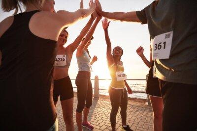 Fototapeta Běžci s vysokým Fiving navzájem po závodě
