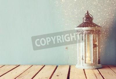 Fototapeta bílým dřevěné vinobraní lucerna s hořící svíčky a větve stromů na dřevěném stole. retro filtruje obraz s třpytkami překrytí