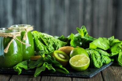 Fototapeta Blended green smoothie s přísadami na kamenné desce, dřevěný stůl selektivní zaměření
