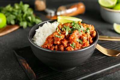 Fototapeta Bowl with tasty chili con carne, rice and lime on dark background, closeup
