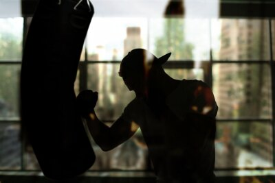 Fototapeta Boxer hits a punching bag against the window, training