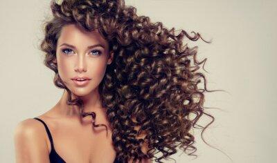 Fototapeta Brunetka s dlouhými a lesklými kudrnatými vlasy. Krásný model s vlnitými účesy.