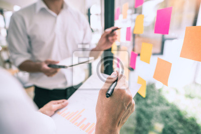 Fototapeta Business people meeting at office and use sticky notes on glass wall in office, diverse employees people group planning work together brainstorm strategy.