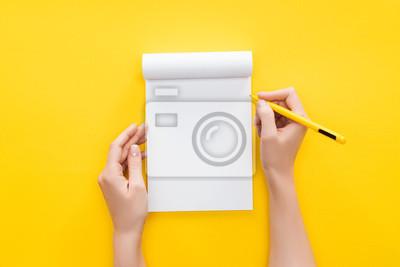 Fototapeta částečný pohled osoba, která drží pero nad prázdný zápisník na žlutém podkladu