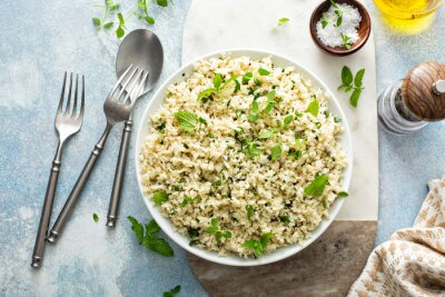 Fototapeta Cauliflower rice with herbs and lemon juice in a white bowl