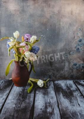 Fototapeta Ceramic jug with spring flowers on wooden table