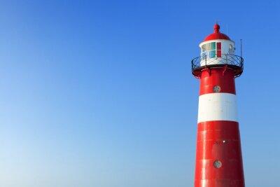 Fototapeta Červené a bílé maják a jasně modré obloze