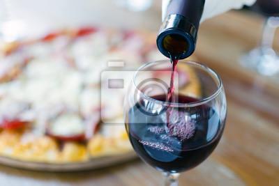 Fototapeta Červené víno se nalévá z lahve do sklenice v restauraci nebo kavárně, v pozadí je silueta pizzy.