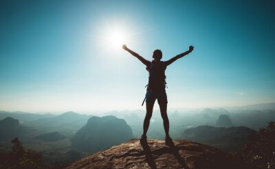 Fototapeta Cheering woman backpacker enjoy the view on sunrise mountain top cliff edge