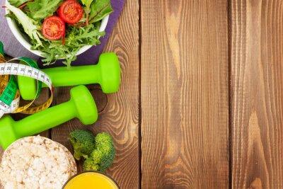 Fototapeta Činky, svinovací metr a zdravé jídlo přes dřevěný stůl