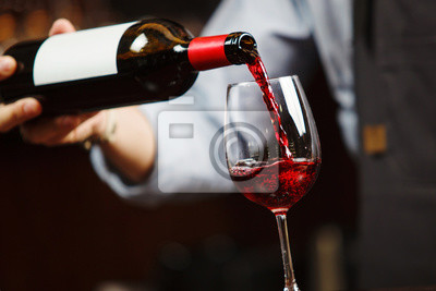 Fototapeta Číšník nalil červené víno do sklenice na víno. Sommelier nalévá alkoholický nápoj