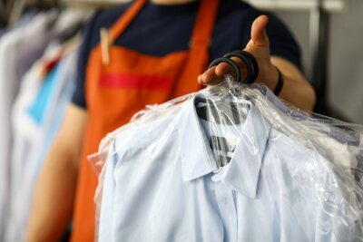 Fototapeta Clothes dry cleaning service worker returning shirts to customer