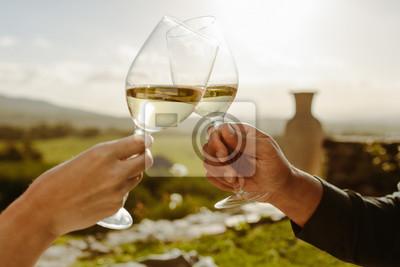 Fototapeta Couple toasting white wine in a vine yard
