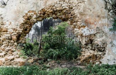 Fototapeta Díra ve stěně opuštěné kamenné budovy.