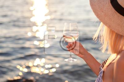 Fototapeta Dívka drží skleničku s bílým vínem v ruce na pláži v létě pozadí slunce moře nebo oceánu. Blond krásná žena je slaměný klobouk je relaxace, pití, cestování a užívat si života na dovolené.