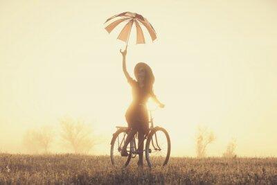 Fototapeta Dívka s deštníkem na kole v přírodě na úsvitu času