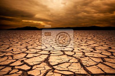 Fototapeta dramatický západ slunce nad popraskané země. Pouštní krajina pozadí.