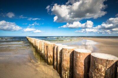Fototapeta Dřevěné vlnolamy na písečné pláži Leba v pozdních odpoledních hodinách, Baltského