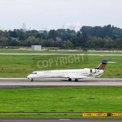 Fototapeta DUSSELDORF, GERMANY - SEPTEMBER 05, 2015: Eurowings Bombardier CRJ-900 NG arrives to the Dusseldorf International Airport.