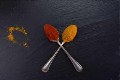 Fototapeta Dva vinobraní lžíce s kořením kari a papriky na černém pozadí.