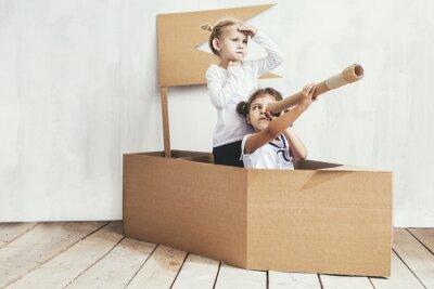 Fototapeta Dvě děti malé holčičky doma v lepenkové lodi hrají kapitány a námořníky