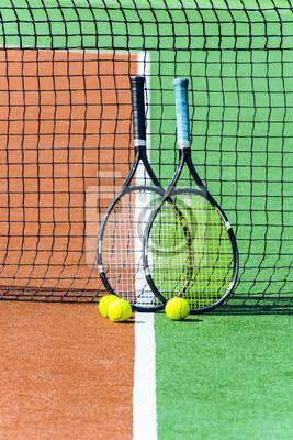 107d3893fc3 Fototapeta Dvě tenisová raketa a míčky. Dvě tenisové rakety se opírají o  tenisovou síť.
