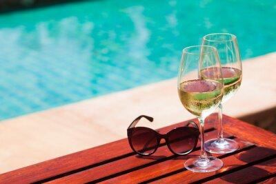 Fototapeta Elegant flute glass of sparkling white wine or champagne by side of swimming pool