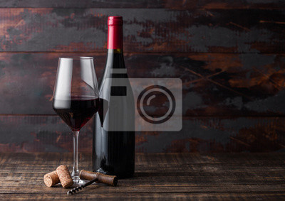 Fototapeta Elegant glass and bottle of red wine with corks and corkscrew on dark wooden background. Natural Light