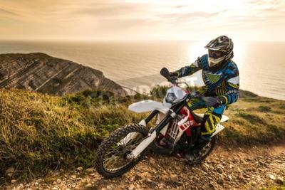 Fototapeta Enduro jezdec lezení strmý svah proti krásný západ slunce na krajina