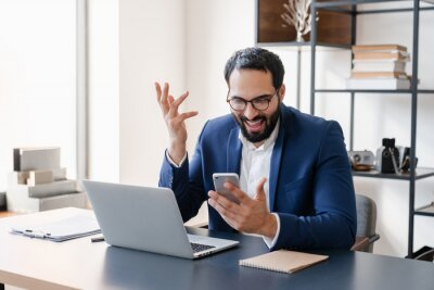 Fototapeta Extremely happy Middle Eastern businessman excited about his achievements using smart phone, getting promotion, salary, successful contract deal. Remote working office at home