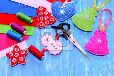 Fototapeta Felt Vánoční ozdoby. Vánoční strom, srdce, hvězda, sněhulák řemesla, nůžky, šití, cítil listy na modrém dřevěném podkladu. Jednoduché děti řemesla