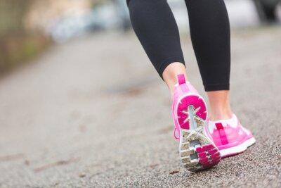 Fototapeta Female Runner Shoes closeup on the road, town setting.