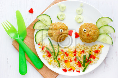 Fototapeta Fish meatballs with porridge and vegetable slices for funny and healthy dinner for kids, food art composition