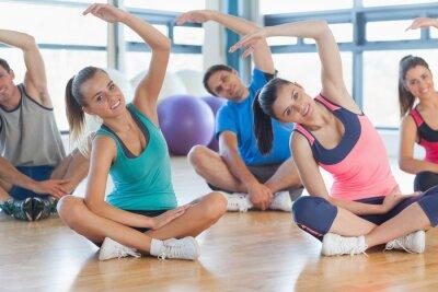 Fototapeta Fitness třídy a instruktor seděli a natahovat ruce