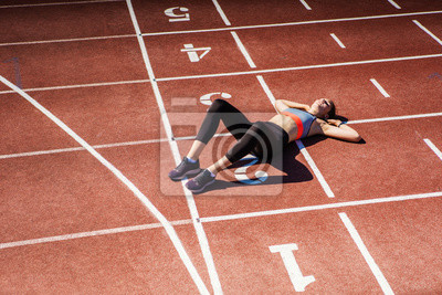 Fototapeta From above view of exhausted teen athlete in sportswear resting on track after finishing tough race