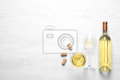 Fototapeta Glasses and bottle with white wine on wooden background, flat lay. Space for text