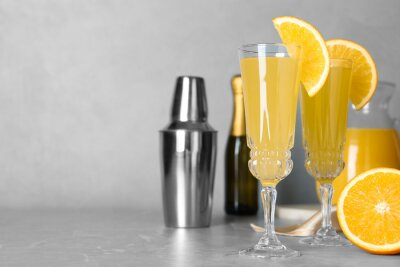 Fototapeta Glasses of Mimosa cocktail with garnish on marble table. Space for text