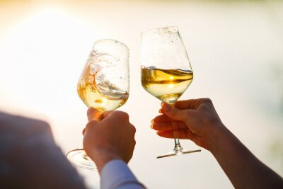Fototapeta glasses with white wine splash in the hands