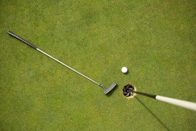 Fototapeta Golf club and golf ball on the putting green beside flag