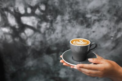 Fototapeta Gray cup of fresh cappuccino in woman hands on background of gray concrete cement textured wall. Trendy hipster cafe design.