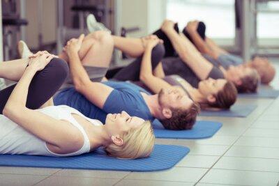 Fototapeta gruppe macht dehnübungen im fitness-center
